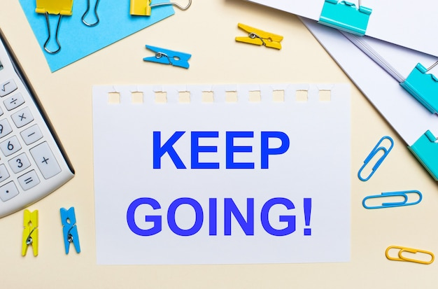 На светлом фоне стопки документов, белый калькулятор, желтые и синие канцелярские скрепки и прищепки, а также записная книжка с надписью keep going.