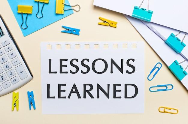 밝은 배경에는 문서 더미, 흰색 계산기, 노란색 및 파란색 종이 클립과 빨래 집게, lessons learned라는 텍스트가있는 노트북이 있습니다.