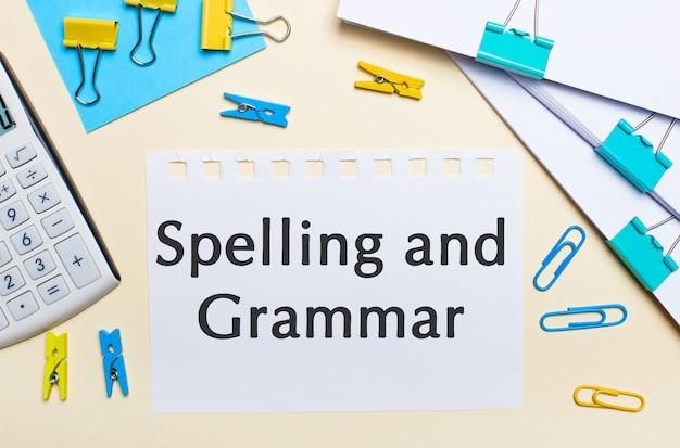 明るい背景には、書類の山、白い電卓、黄色と青のペーパークリップと洗濯バサミ、そして「スペルと文法」というテキストが書かれたノートがあります。