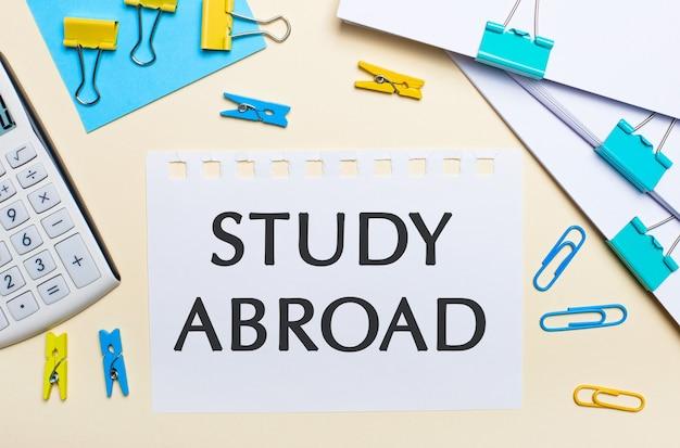 明るい背景には、書類の山、白い電卓、黄色と青のペーパークリップと洗濯バサミ、そして「studyabroad」というテキストが書かれたノートがあります。