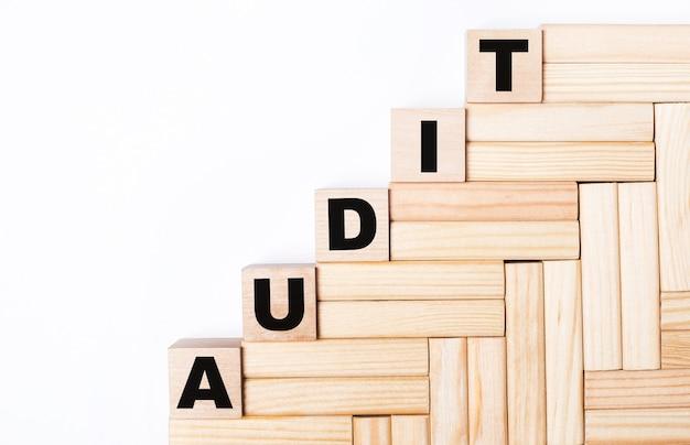 На светлом фоне деревянные блоки и кубики с текстом audit.