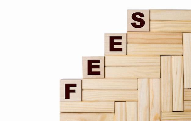 明るい背景に、feesというテキストが付いた木製のブロックと立方体