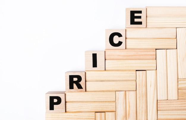 На светлом фоне деревянные блоки и кубики с текстом цена.