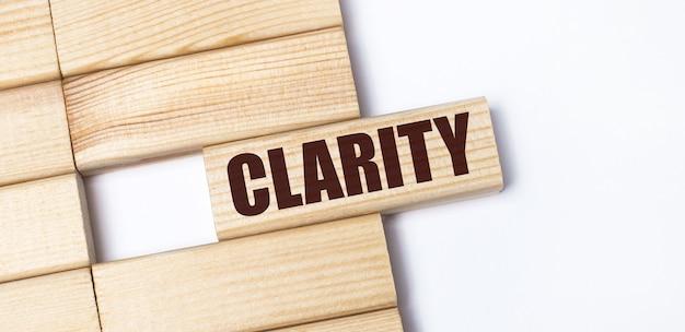 明るい背景に、clarityというテキストが付いた木製のブロック。クローズアップ上面図。