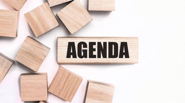 明るい背景に、木製の立方体と「agenda」というテキストの付いた木製のブロック。上から見る