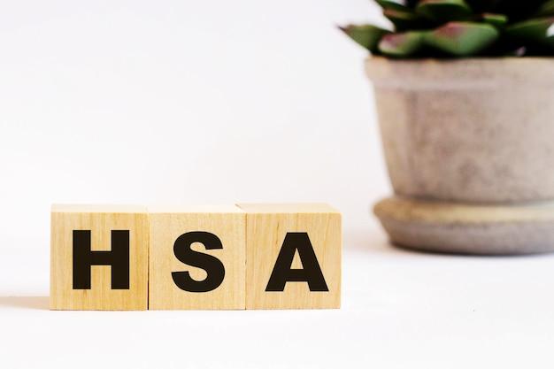 На светлом фоне деревянные кубики с надписью hsa и цветок в горшке. расфокусировать