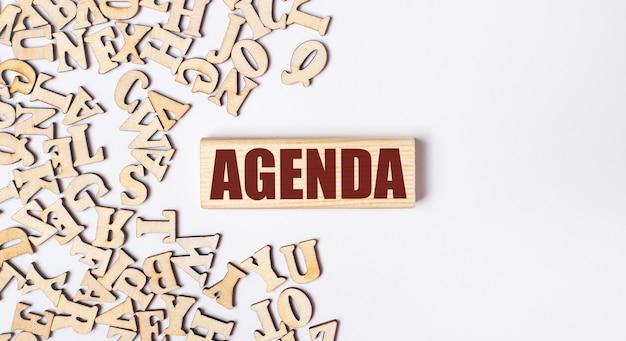 明るい背景に、木製の文字と「agenda」というテキストが書かれた木製のブロック。フラットレイ