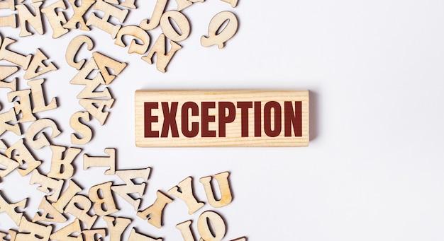 На светлом фоне деревянные буквы и деревянный блок с текстом exception. плоская планировка