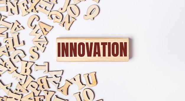На светлом фоне деревянные буквы и деревянный блок с текстом инновации. плоская планировка