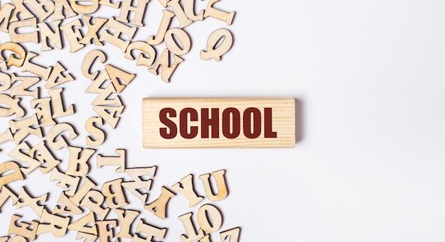 明るい背景に、木製の文字と「学校」というテキストが書かれた木製のブロック。フラットレイ