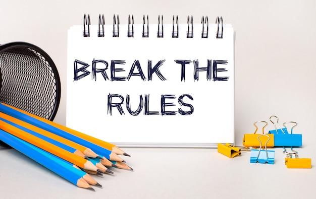 На светлом фоне желтые и синие карандаши и скрепки и белый блокнот с текстом нарушить правила.