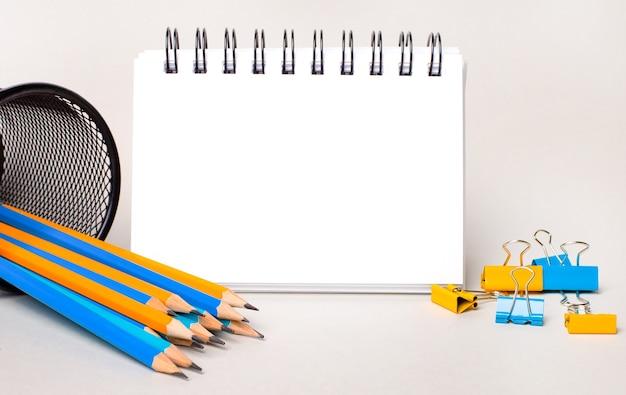 明るい背景に、黄色と水色の鉛筆とペーパークリップ、およびテキストを挿入する場所のある白い空白のノートブック。レンプレート