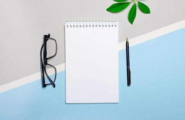 水色と灰色の背景に、眼鏡、ペン、緑の植物、テキストやイラストを挿入する場所のある白いノート。テンプレート。フラットレイ