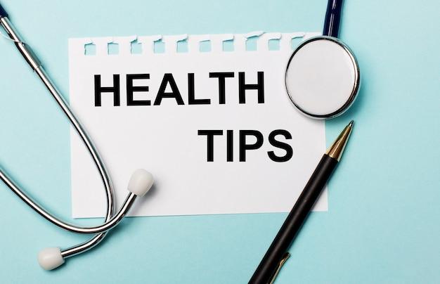水色の背景に、聴診器、ペン、そして健康の秘訣が刻まれた一枚の紙
