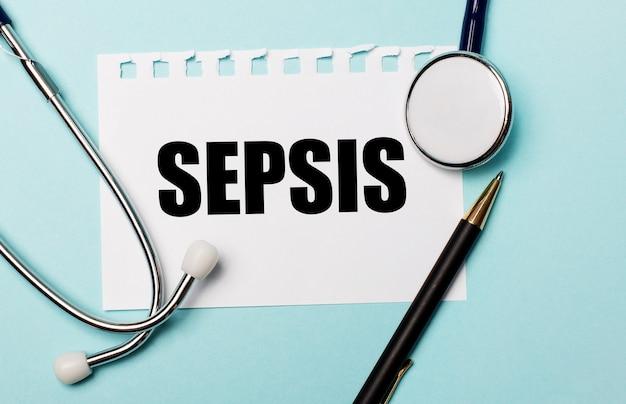 На голубом фоне стетоскоп, ручка и лист бумаги с надписью sepsis. медицинская концепция