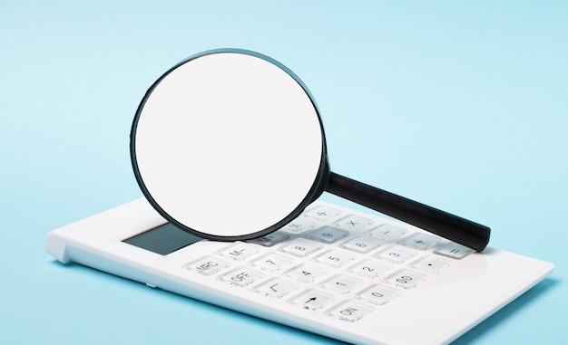 水色の背景に、白い電卓とテキストを挿入する場所のある虫眼鏡。レンプレート。ビジネスコンセプト