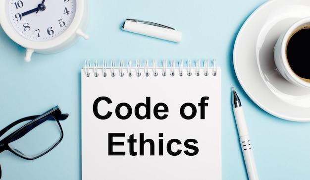 水色の背景に、コーヒーの入った白いカップ、白い目覚まし時計、白いペン、「倫理規定」というテキストのノート。上から見る