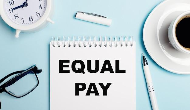 На голубом фоне белая чашка с кофе, белый будильник, белая ручка и блокнот с текстом equal pay. вид сверху