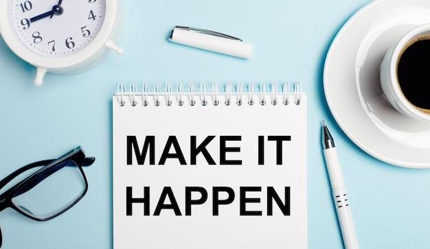 На светло-голубом фоне белая чашка с кофе, белый будильник, белая ручка и блокнот с надписью make it happen
