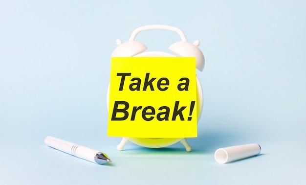 На голубом фоне - белая ручка и будильник с наклеенной на нее ярко-желтой наклейкой с текстом take a break.