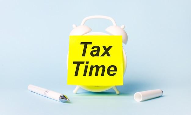 На голубом фоне - белая ручка и будильник с наклеенной ярко-желтой наклейкой с текстом налоговое время.