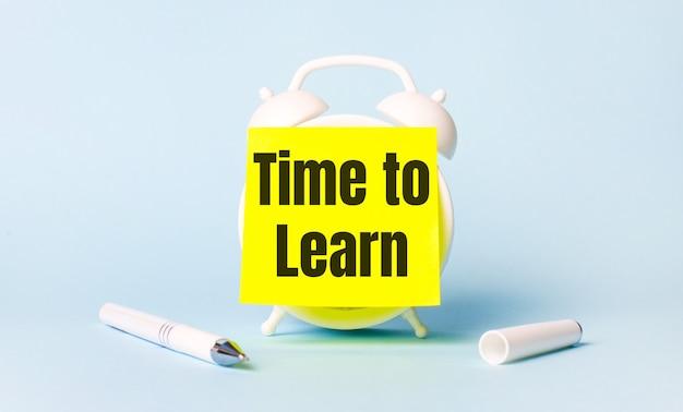 На голубом фоне - белая ручка и будильник с наклеенной ярко-желтой наклейкой с текстом «время учиться».