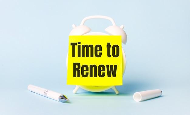 На голубом фоне - белая ручка и будильник с наклеенной на нее ярко-желтой наклейкой с надписью time to renew.