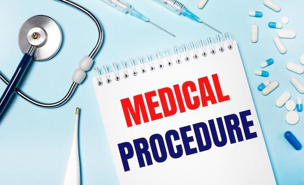 На голубом фоне электронный градусник, стетоскоп, бело-синие таблетки, шприцы и блокнот с текстом медицинская процедура. медицинская концепция