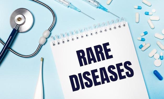 На голубом фоне электронный градусник, стетоскоп, бело-синие таблетки, шприцы и блокнот с надписью редкие заболевания. медицинская концепция