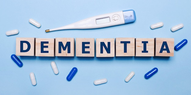 水色の背景に、電子体温計、白と青の丸薬、認知症の碑文が書かれた木製の立方体。医療コンセプト