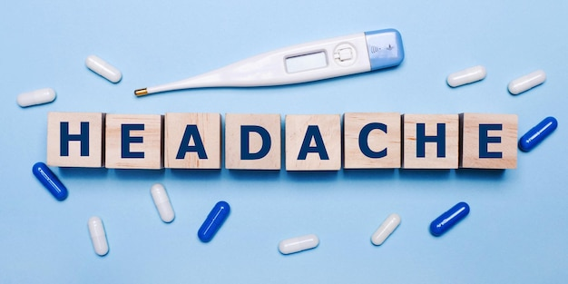 На голубом фоне электронный градусник, бело-синие таблетки и деревянные кубики с надписью головная боль. медицинская концепция