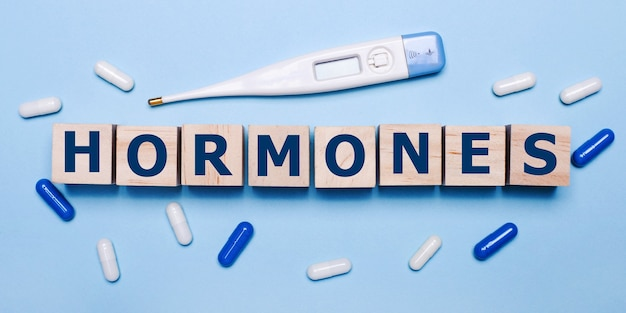 밝은 파란색 배경에 전자 온도계, 흰색 및 파란색 알약, hormones라는 글자가 있는 나무 큐브. 의료 개념