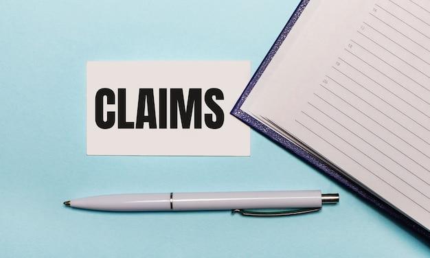 На голубом фоне открытая тетрадь, белая ручка и карточка с текстом претензии. вид сверху