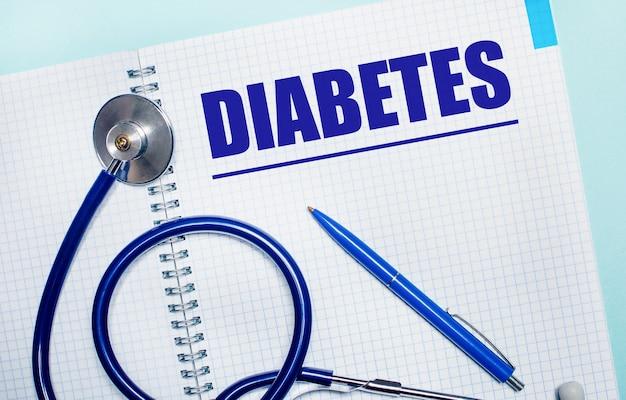 На голубом фоне открытая тетрадь со словом диабет, синяя ручка и стетоскоп. вид сверху. медицинская концепция
