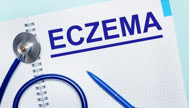 На голубом фоне открытая тетрадь со словом экзема, синяя ручка и стетоскоп. вид сверху. медицинская концепция