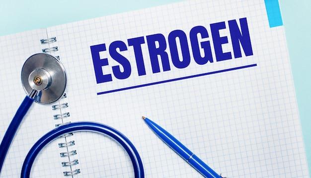 水色の背景に、エストロゲンという言葉が書かれた開いたノートブック、青いペン、聴診器。上からの眺め。医療コンセプト