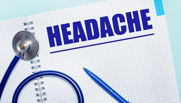 На голубом фоне открытая тетрадь со словом головная боль, синяя ручка и стетоскоп. вид сверху. медицинская концепция