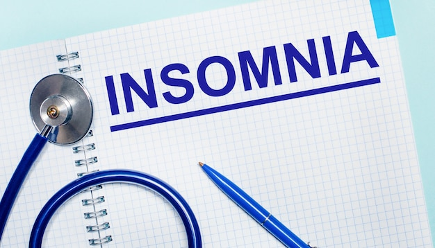 연한 파란색 배경에 insomnia라는 단어가 있는 노트북, 파란색 펜, 청진기가 있습니다. 위에서 볼 수 있습니다. 의료 개념