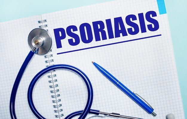 На голубом фоне открытая тетрадь со словом псориаз, синяя ручка и стетоскоп. вид сверху. медицинская концепция