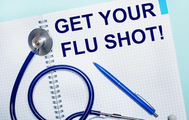 水色の背景に、get your flu shotという言葉が書かれた開いたノートブック、青いペン、聴診器。上からの眺め。医療の概念