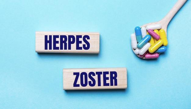 水色の背景に、スプーンに入った明るいマルチカラーの錠剤と、帯状疱疹のテキストが書かれた2つの木製ブロック。医療の概念
