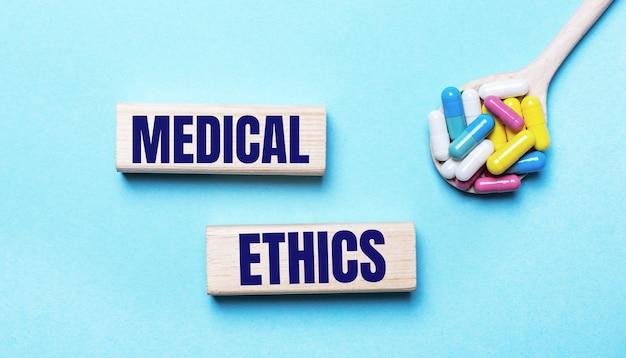 На голубом фоне яркие разноцветные таблетки в ложке и два деревянных кубика с надписью медицинская этика. медицинская концепция