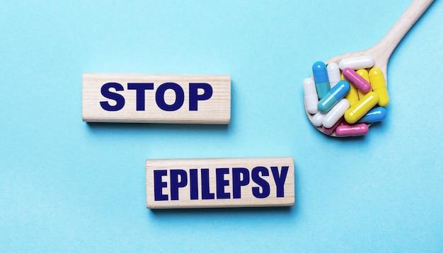 水色の背景に、スプーンの明るいマルチカラーの錠剤と2つの木製のブロックに「stopepilepsy」というテキストが表示されます。医療コンセプト
