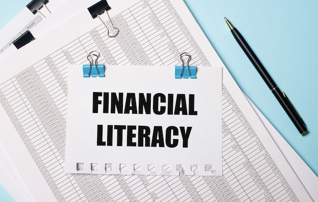 水色の背景に、ドキュメント、ペン、青いペーパークリップにfinancialliteracyというテキストが付いた紙。ビジネスコンセプト。