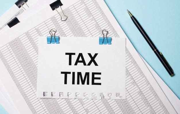 На голубом фоне документы, ручка и лист бумаги на синих скрепках с текстом налоговое время. бизнес-концепция.