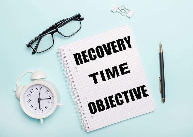 水色の背景には、黒い眼鏡とペン、白い目覚まし時計、白いペーパークリップ、「回復時間の目的」という言葉が書かれたノートがあります