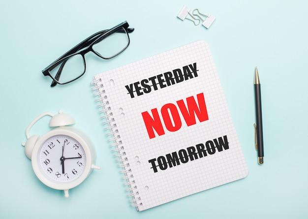 水色の背景には、黒い眼鏡とペン、白い目覚まし時計、白いペーパークリップ、そしてyesterday nowtomorrowという言葉が書かれたノートがあります。ビジネスコンセプト