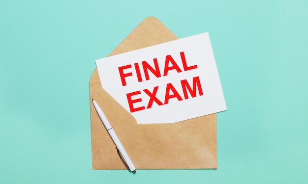 水色の背景には、開いたクラフト封筒、白いペン、テキストfinalexamの白い紙があります。