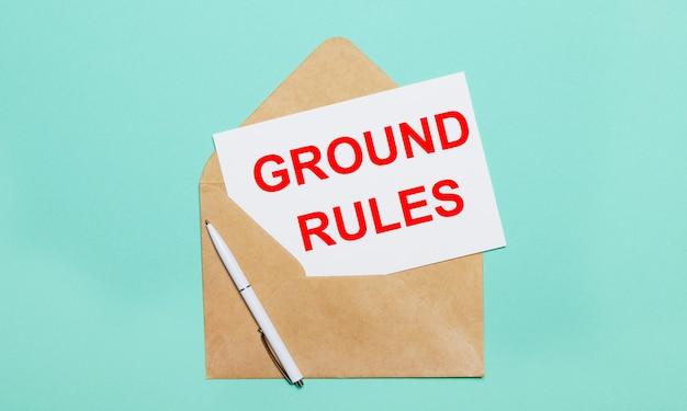 水色の背景には、開いたクラフト封筒、白いペン、「groundrules」というテキストが書かれた白い紙があります。