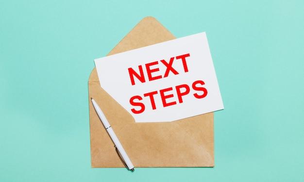 水色の背景には、開いたクラフト封筒、白いペン、テキストが書かれた白い紙があります。次のステップ